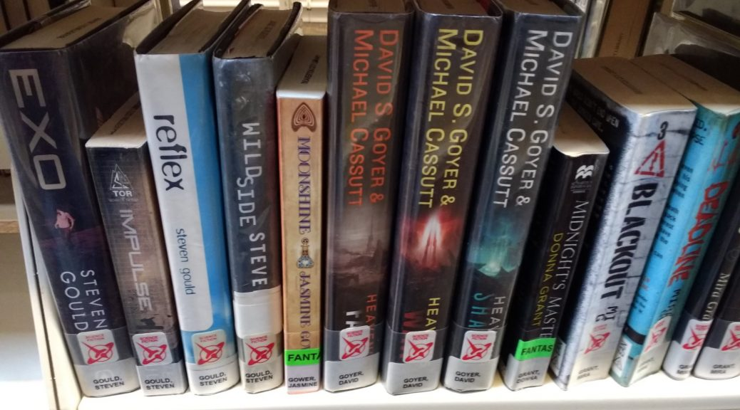 A copy of Moonshine sitting on a public library shelf among other books