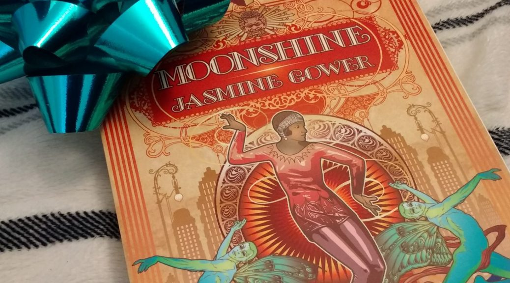A copy of MOONSHINE with a teal ribbon on it